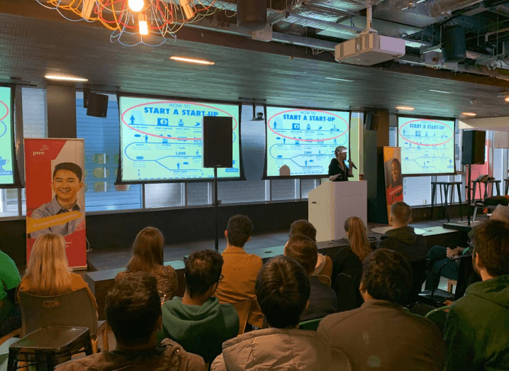 A person standing at a podium on stage making a presentation to a group of young people in front of a screen that has instructions on how to start a start-up.