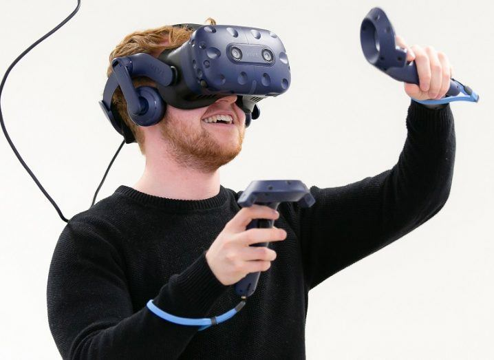 Person in black top smiling while wearing a VR headset and holding controllers.