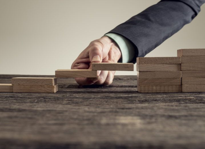A business person is forming a bridge of wooden building blocks in a gap in a set or steps, representing a skills or talent gap.