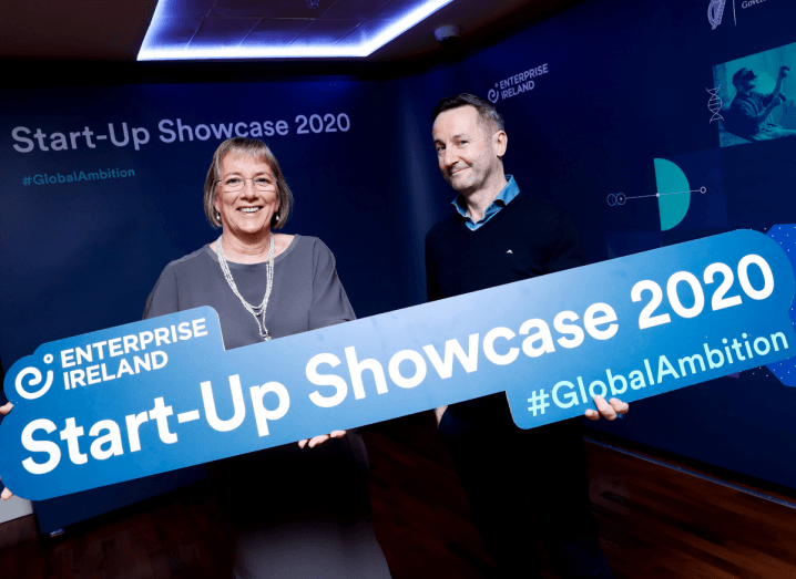 A woman wearing a grey dress and white necklace with short blonde hair stands beside a man in a navy jumper and blue shirt. They are both holding a sign that says Start-up Showcase 2020.
