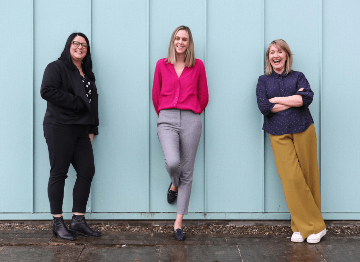 Three women standing in front of a blue wall. The woman on the left is wearing all black and black boots. The woman in the middle is wearing a bright pink cardigan and grey trousers. The woman on the right is wearing a navy blouse and mustard trousers.