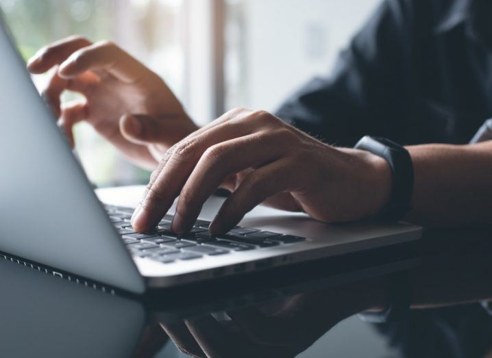 A close-up shot of hands typing on a laptop, representing the need to have avoid a data breach.