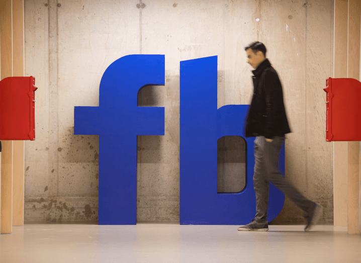 The Facebook logo on a wall in a grey concrete room where a man is walking past wearing a black jumper and blue jeans.