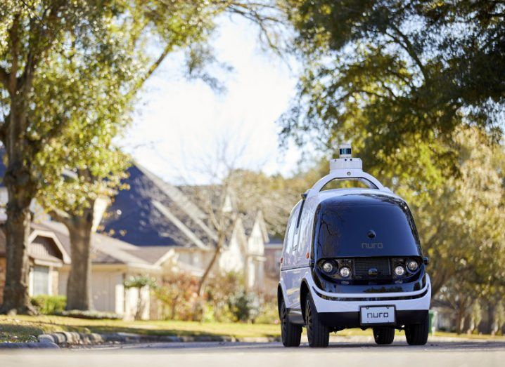A small driverless vehicle travels down a tree-lined residential road.