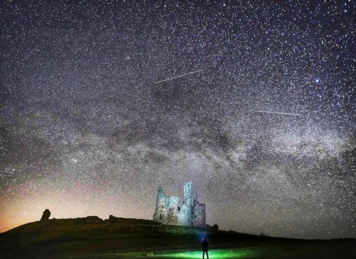 A castle on a hill sits underneath a starry night sky, while a person standing below the castle is bathed in green light.