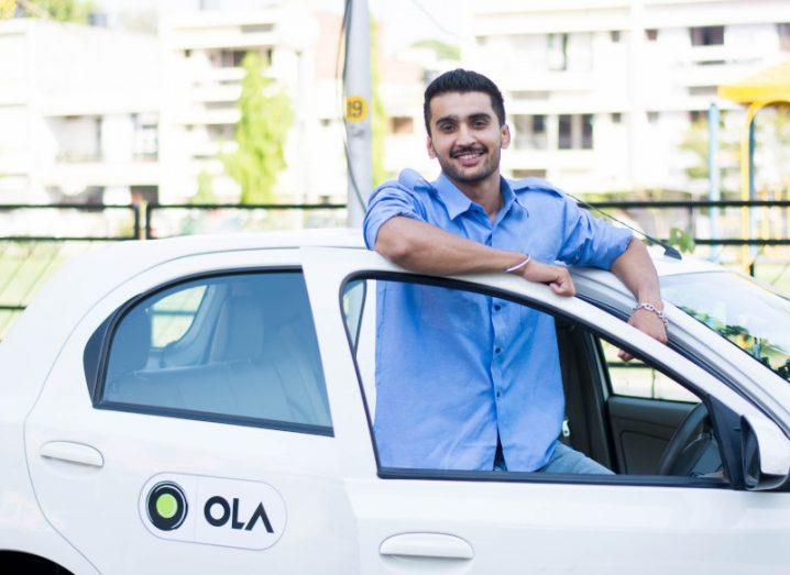 A man in a blue shirt stands leaning against the door of a white car that says 'Ola' on the side.