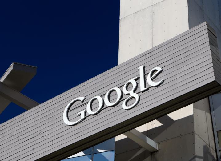 The Google logo on the facade of a grey building under a blue sky.