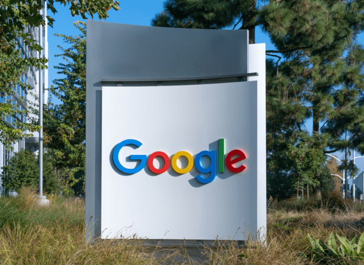 The Google logo on a white pillar in front of grasses and trees.