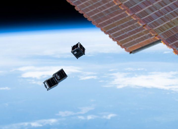 Three cubesats being deployed into orbit with a solar panel of the ISS visible in the top-right corner.
