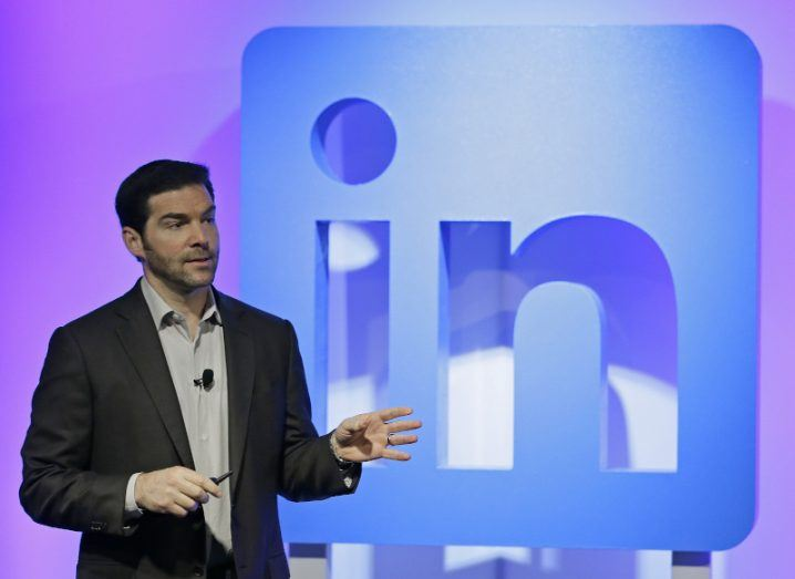 A man in a dark suit stands in front of a large blue and purple LinkedIn logo.