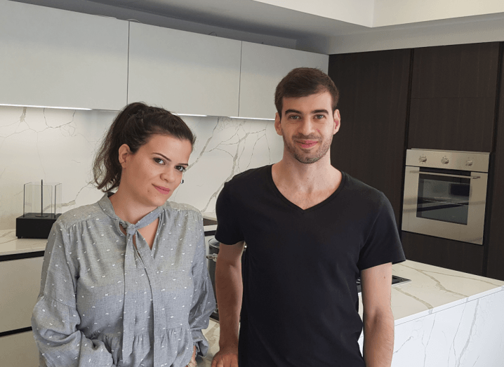 A woman in a grey blouse with white polka dots wears her brown hair in a ponytail. To her right is a man in a black t-shirt who has short brown hair and stubble. They are both standing in a modern, white kitchen with dark brown cabinets on one wall.