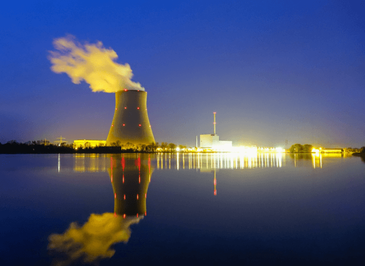 A nuclear power plant in front of a body of water at night.