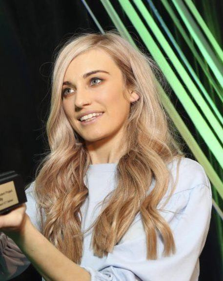 Niamh Donnelly, a young woman with long blonde hair, is pictured receiving an award on stage.
