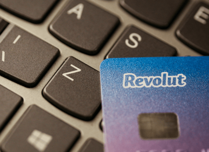 A Revolut payments card on a laptop keyboard. The card is blue and pink.