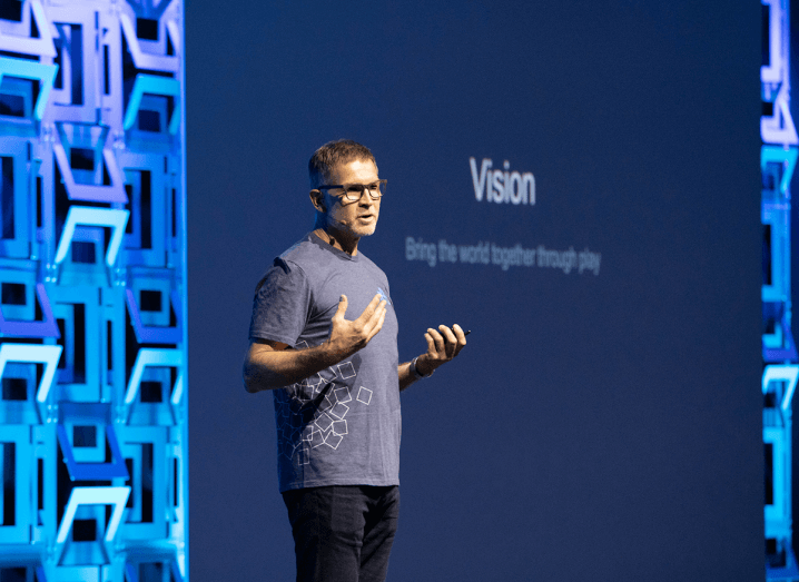 "A man in a blue T-shirt and black jeans stands on stage in front of a projection that says ""Vision"" on a screen behind him. He has his hands turned up and is holding them in front of his body. He has grey hair and is wearing glasses."