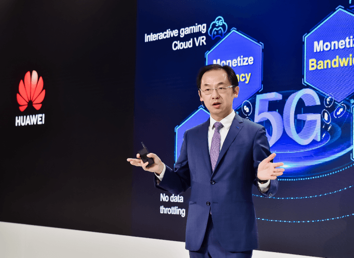 A man in a navy suit stands in front of a projector screen with the Huawei logo on it, beside various facts about 5G.