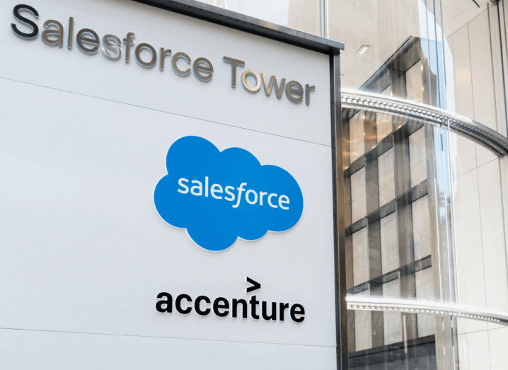 A white sign with the Salesforce and Accenture logos displayed on it outside of a glass building, which is the Salesforce tower in San Francisco.
