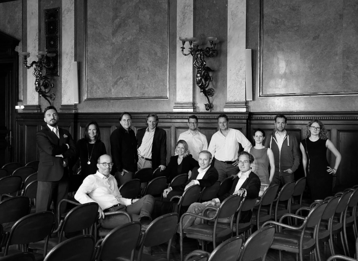 A large group of men and women stand in a room together in front of rows of chairs. Some of the people are sitting on the chairs. The photograph is in black and white.