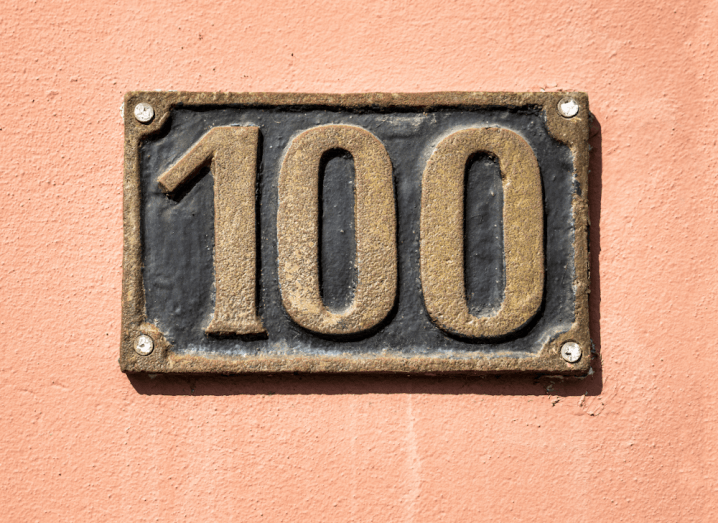 The number 100 on a metal plate in front of a peach-coloured wall.
