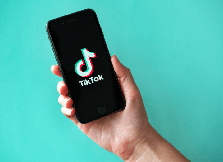 A person holding a phone with the TikTok logo displayed on it in front of a turquoise background.