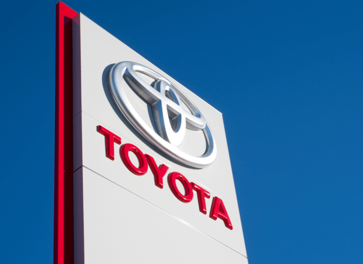 The Toyota logo displayed on a sign in front of a bright blue sky.