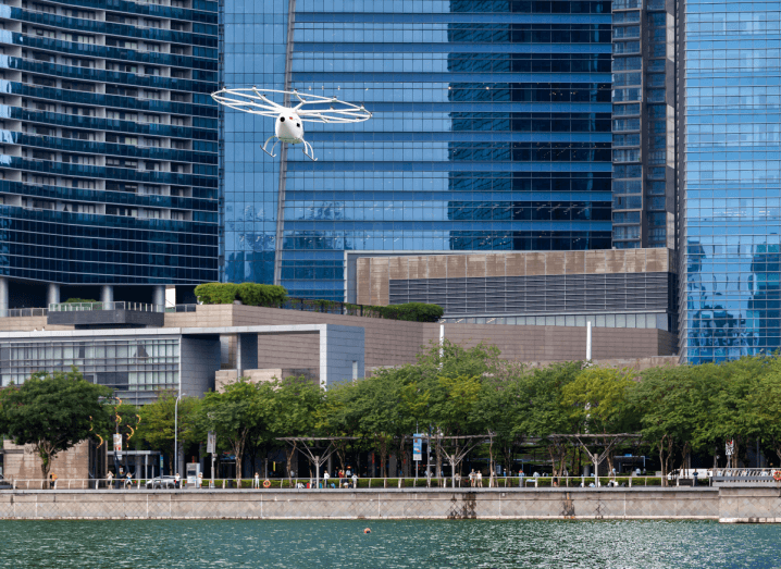 A white aircraft resembling a helicopter flying over a body of water in front of sky scrapers.