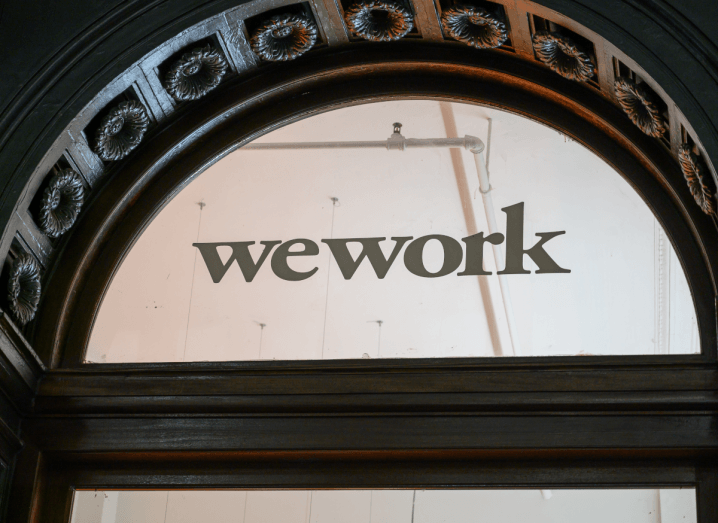 The WeWork logo displayed inside a glass window.