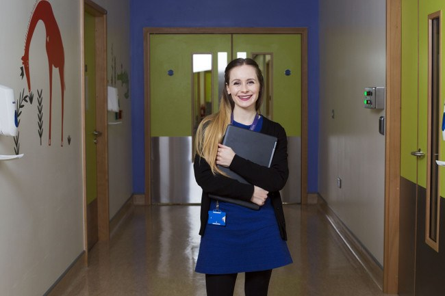A young woman stands in a hospital corridor smiling and holding a closed laptop.