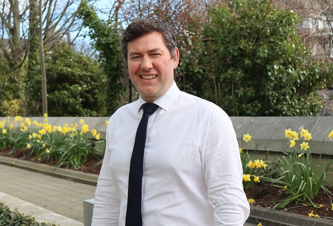 John Lowry smiling in a white shirt and black tie against a background of daffodils and trees.
