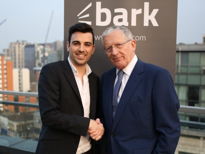 Two men standing beside each other in front of a grey sign that says Bark.