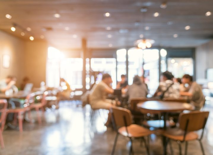 Blurred image of a coffee shop with people at some tables and others empty.