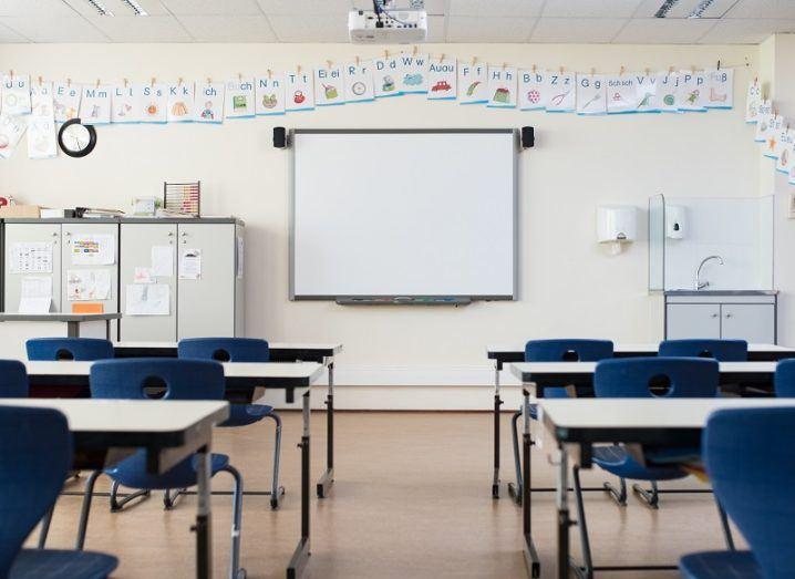School desks in an empty classroom facing a whiteboard.