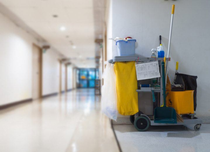 A hospital cleaning trolley equipped with a bucket, mop and other tools, parked beside an empty corridor.