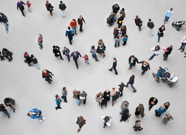 A crowd of people photographed from above. There are a few dozen people walking around on a grey floor.