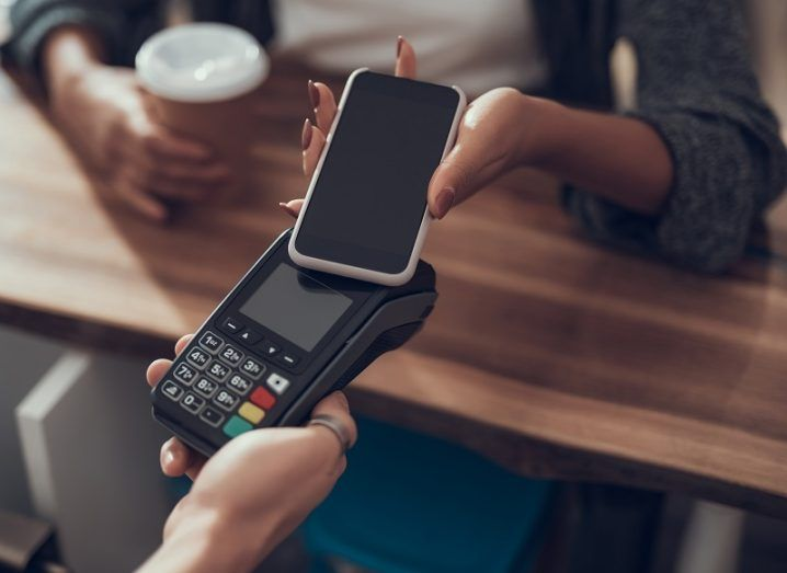 Woman making a contactless payment through her phone at a coffee shop payment terminal.