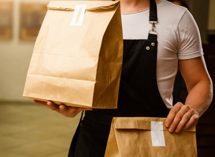 A person wearing a black apron and a white T-shirt holds two brown paper bags.