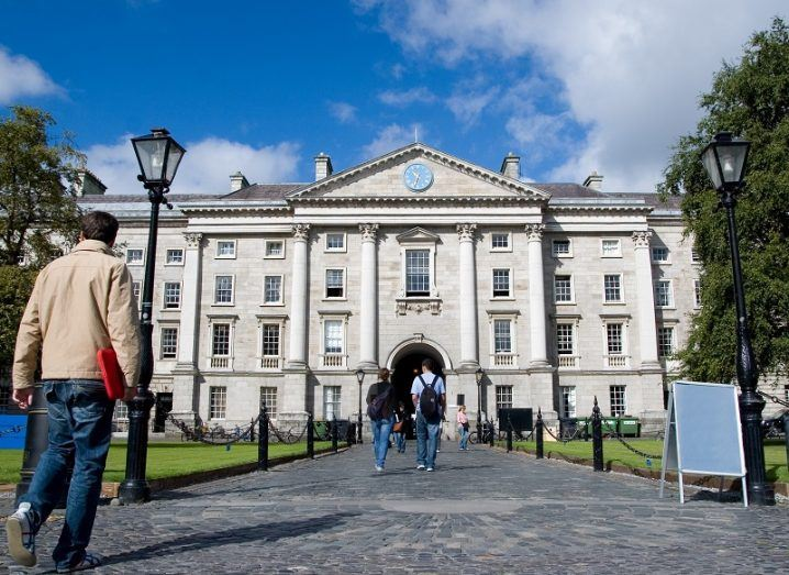Cobbled path at the front entrance to Trinity College Dublin from the main square on a sunny day.