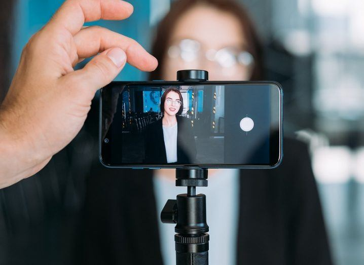 Woman wearing a black blazer and glasses standing in front of a smartphone camera with another hand about to press record.