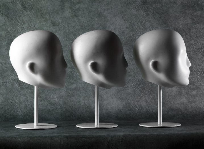 A row of three white plaster mannequin heads, all facing to the right against a grey-green stone background.