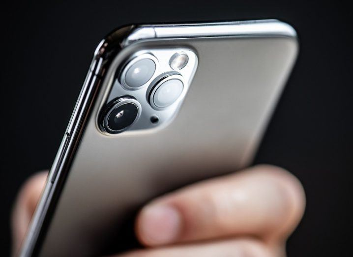 Rear of the iPhone 11 being held in a person's hand against a black background.