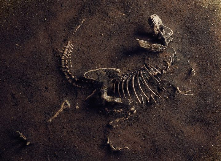 3D render of a dimly-lit fossilised T-rex in brown dirt.