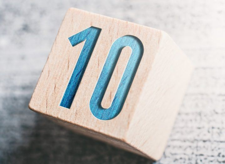 The number 10 in blue writing on a wooden block on a stone table.