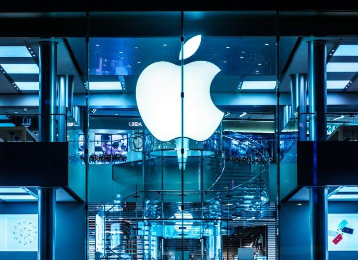 The Apple logo lit on a glass wall of its Hong Kong store at night.
