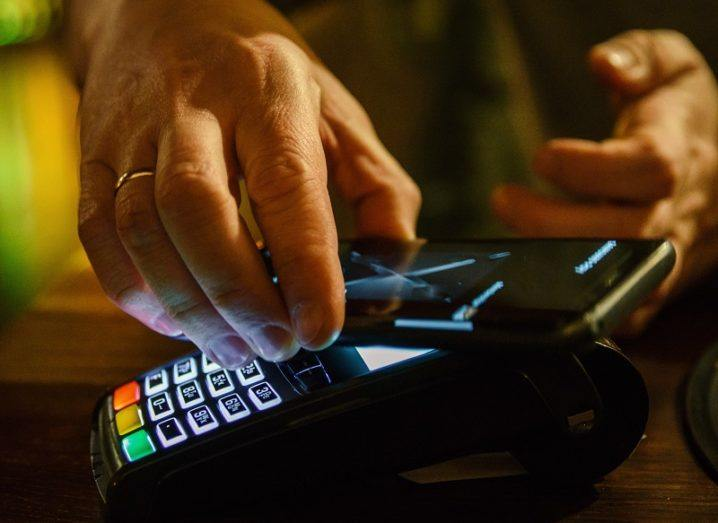 Hand of a person using a contactless payment machine with their phone.
