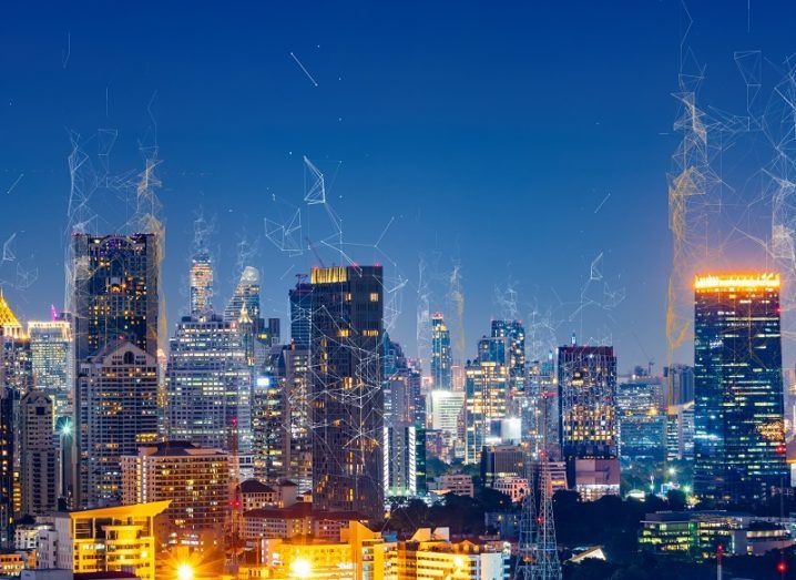 Concept of a large city at night with data bring transmitted across vast IoT networks.