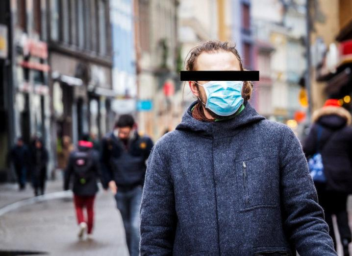 A young man in winter clothes and a surgical mask walks down a busy shopping street. The image has been edited to place a black bar across his eyes in order to preserve his identity.
