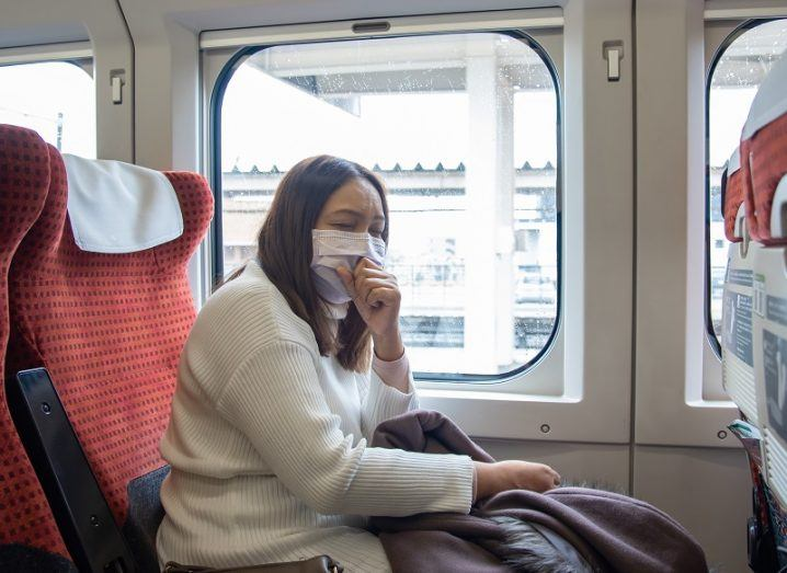 Woman on a train wearing a face mask.