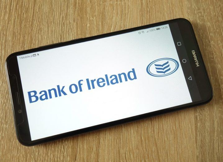 Phone on a wooden table with the Bank of Ireland logo on the screen.