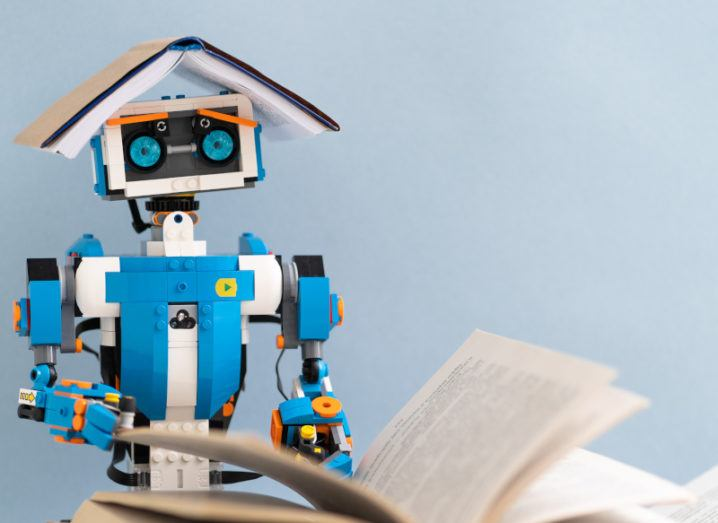 Small blue robot with a book on its head while it is reading another.