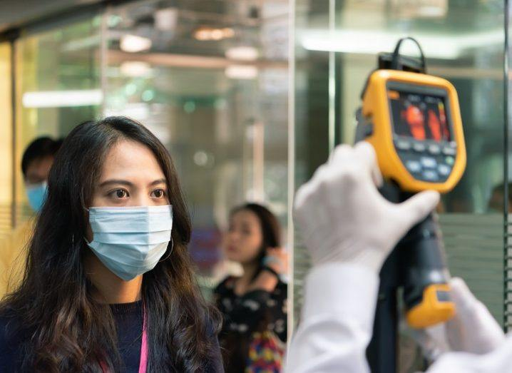 Woman wearing a face mask being screened for her temperature by a device.